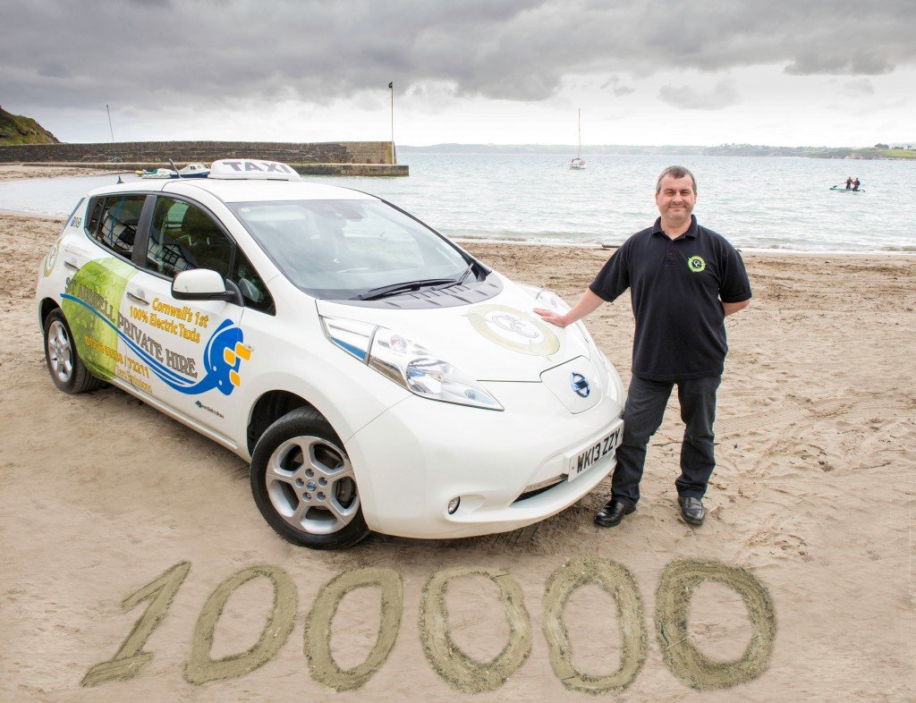 Man stands beside Nissan Leaf electric taxi parked on beach